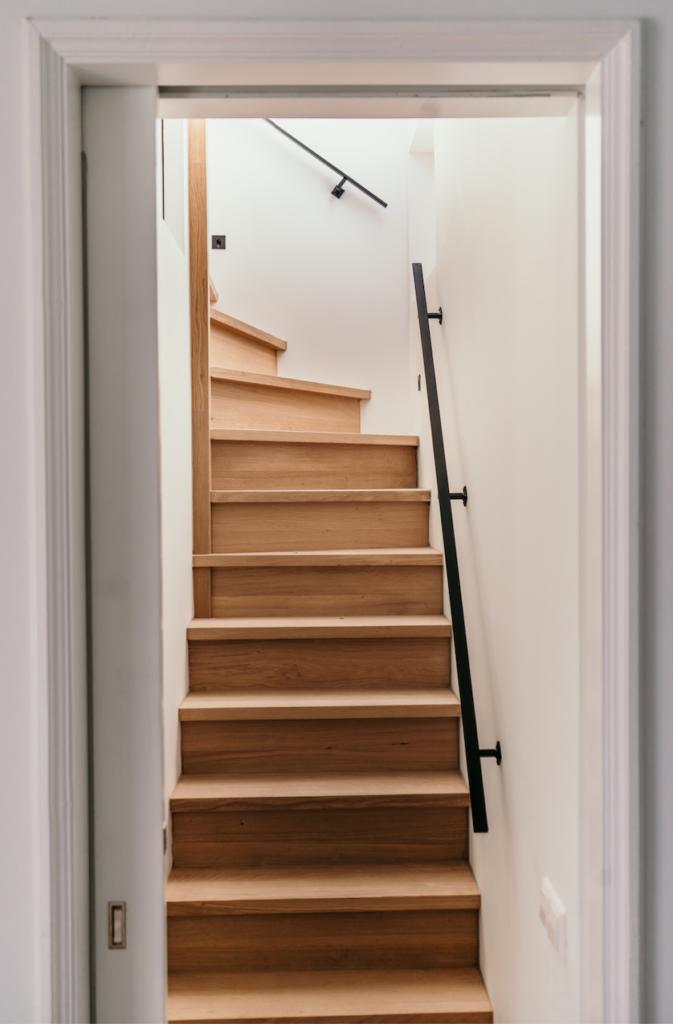 Trap naar de dakopbouw, eikenhouten trap, zwart stalen leuning en trapverlichting