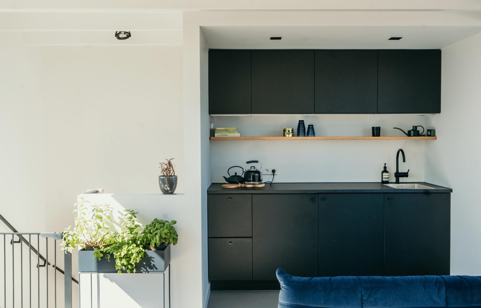 Zwarte Ikea keuken met eikenhouten plank